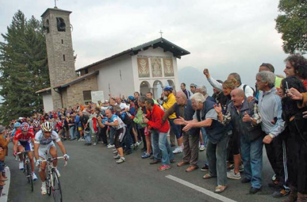 Bettini leads the breakaway group as they pass a church. Photo copyright Fotoreporter Sirotti.